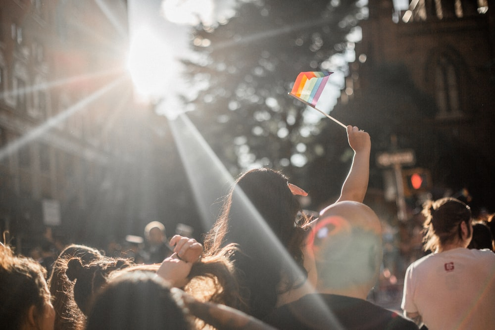 woman raising rainbow flag in crowd