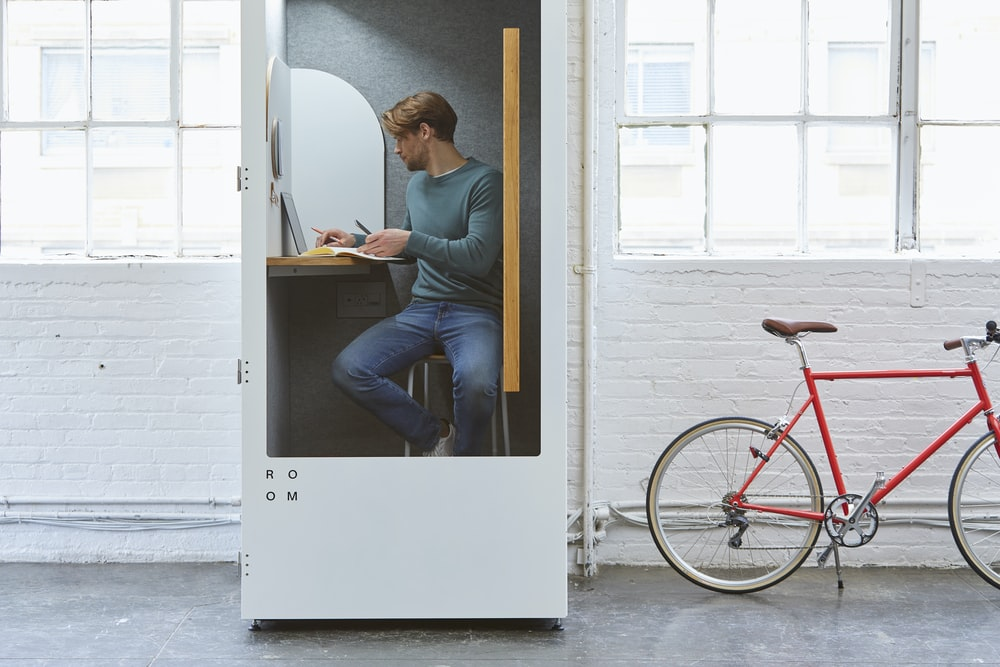 man sitting inside wooden cubicle with red bicycle parked outside