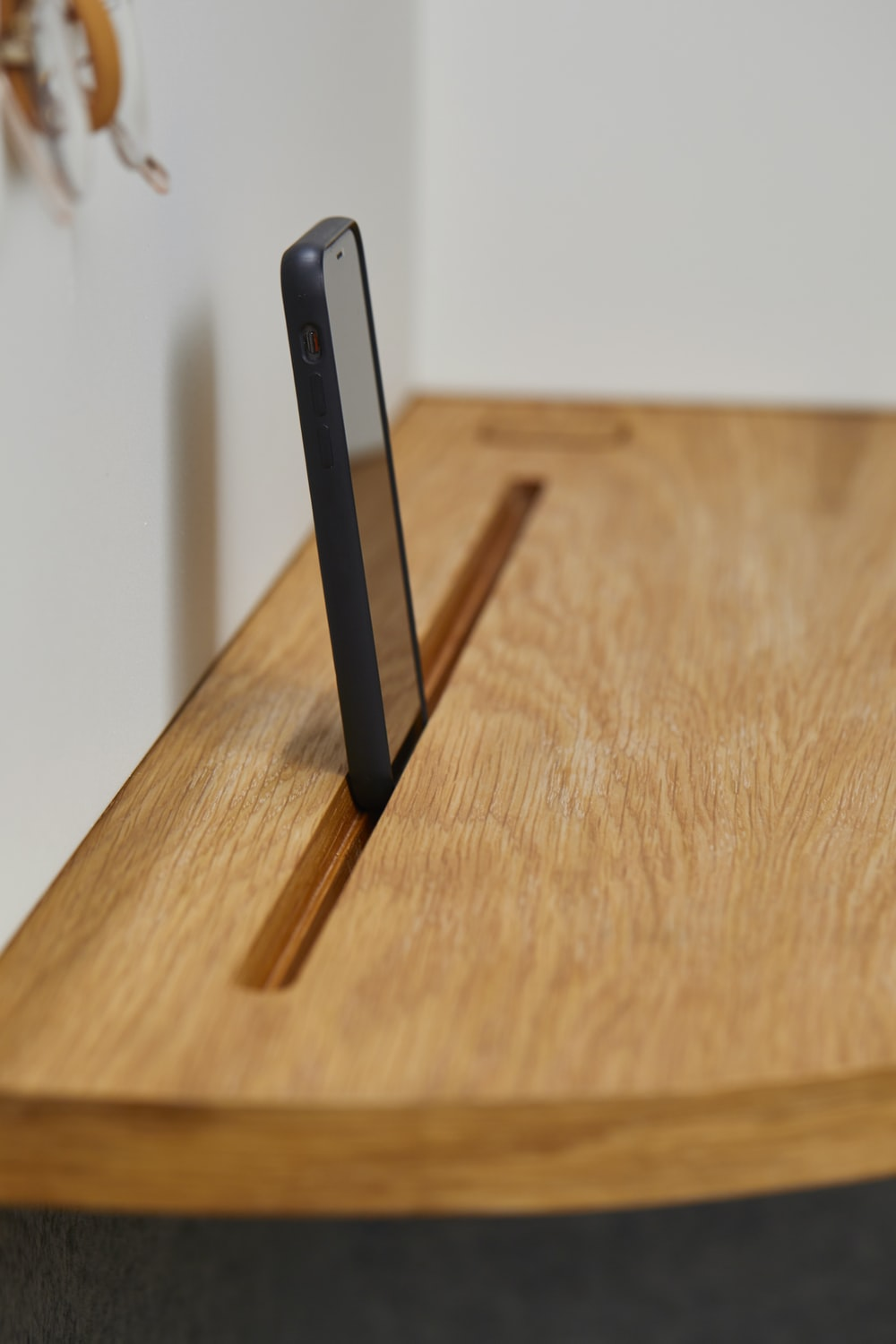 black smartphone on brown shelf