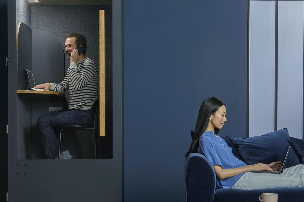 men in a room using phone near a women using a laptop close-up photography
