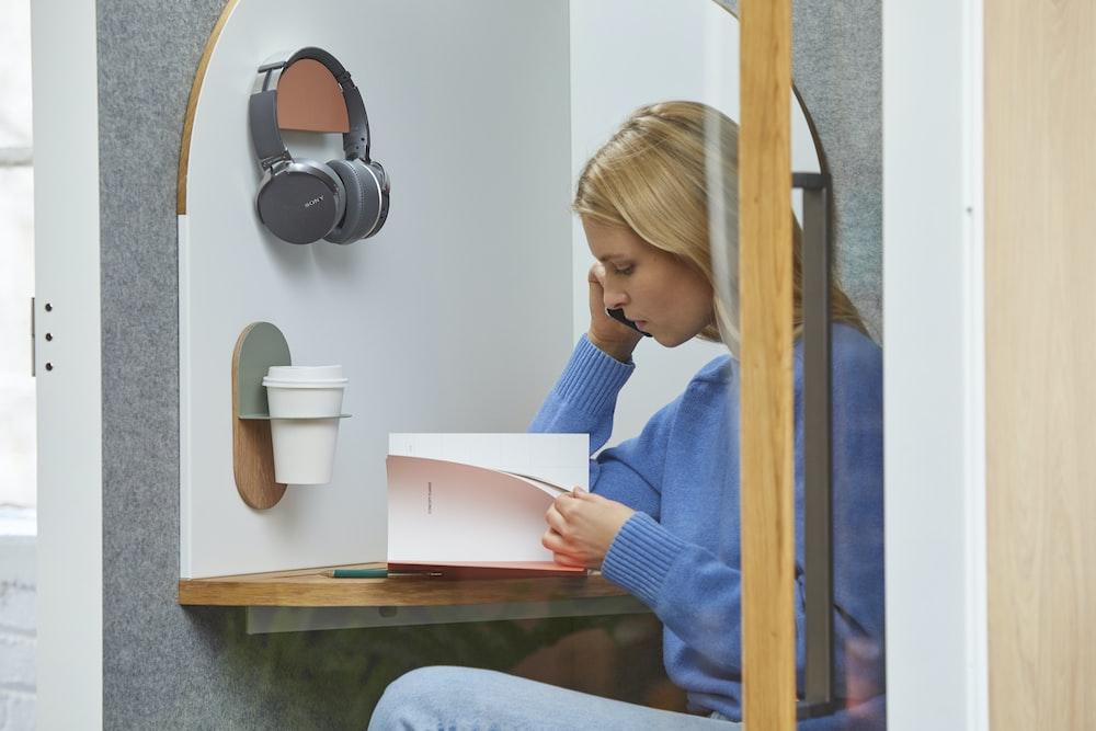 sitting woman wearing gray sweater reading book