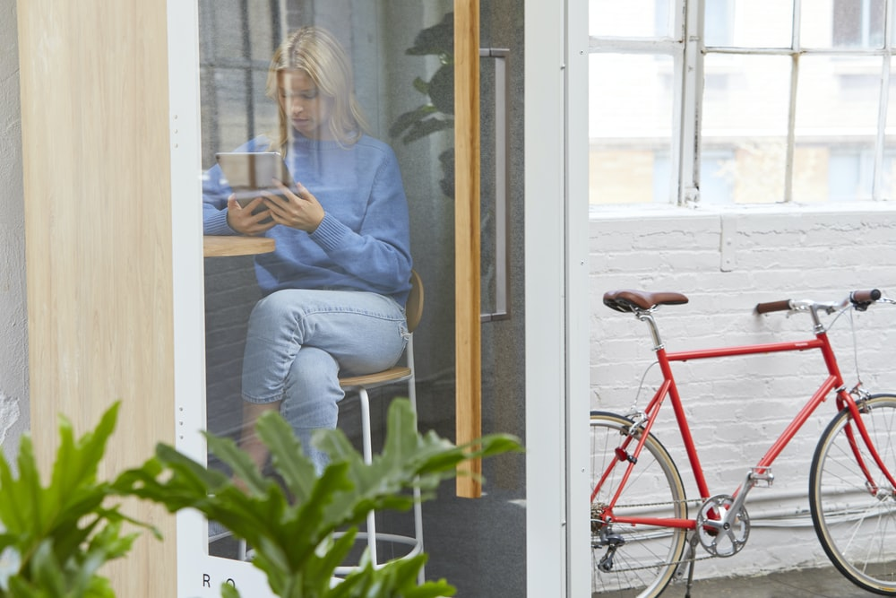 red bicycle parked outside room with sitting woman reading book