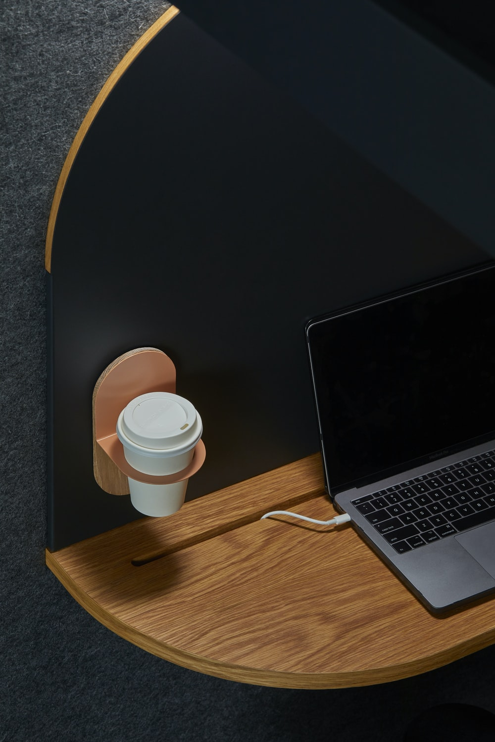 black laptop computer on brown table beside hanged white cup