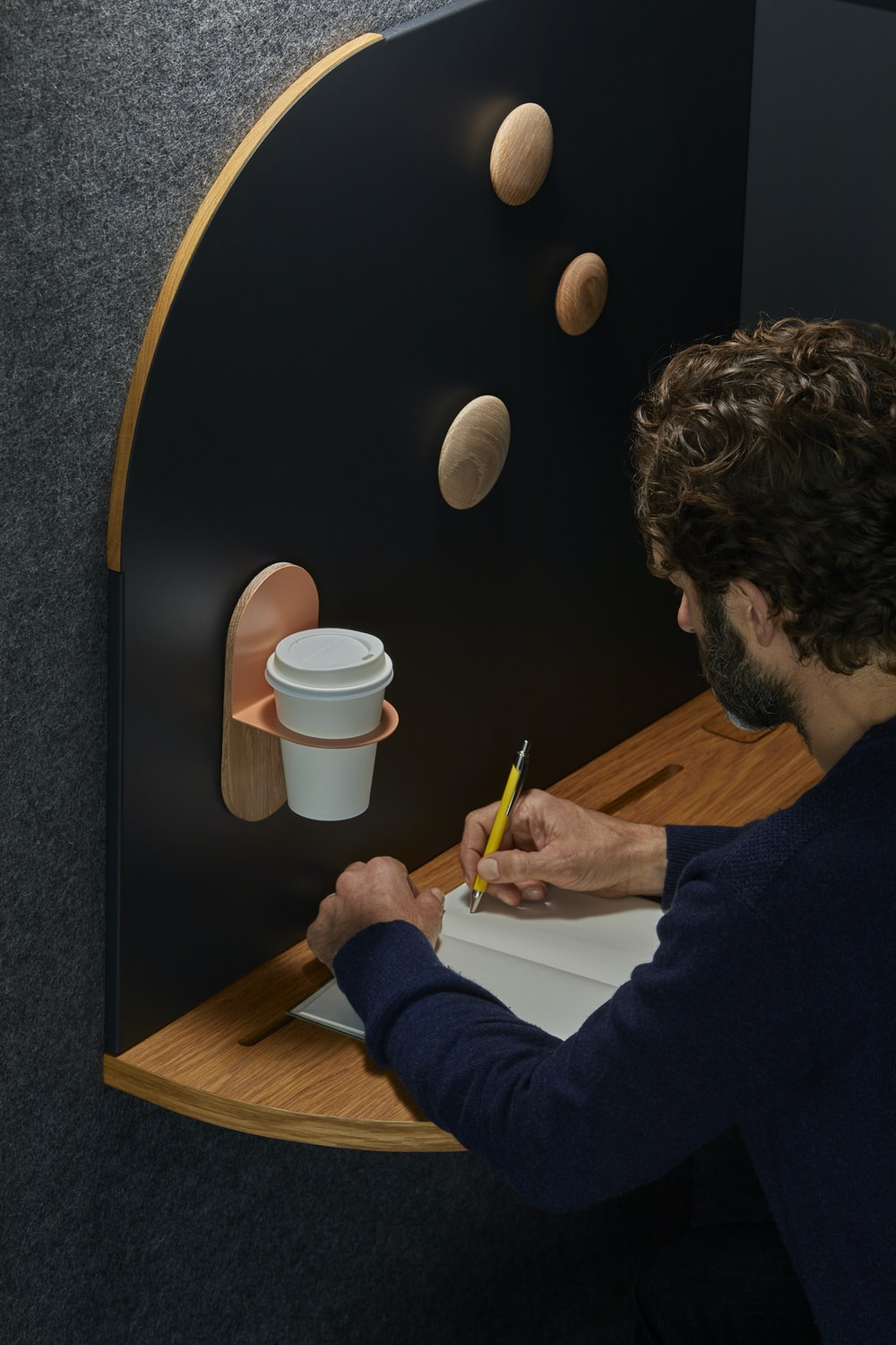 man writing on notebook on wooden desk and coffee place on the wall