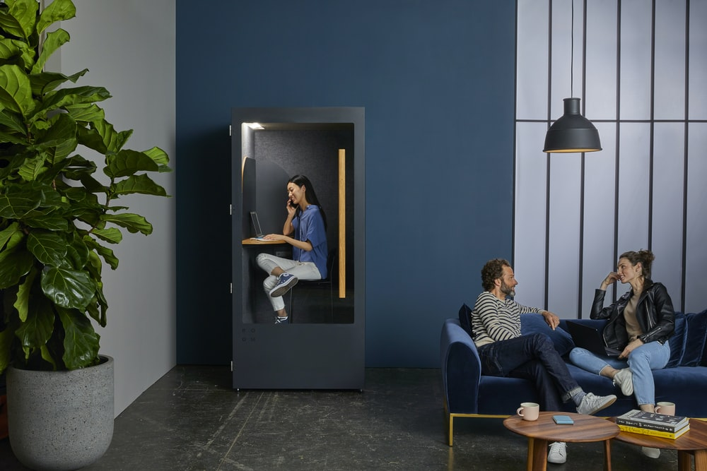 woman in black leather jacket leaning on sofa sitting and facing man in blue denim jeans near woman in blue shirt inside cubicle