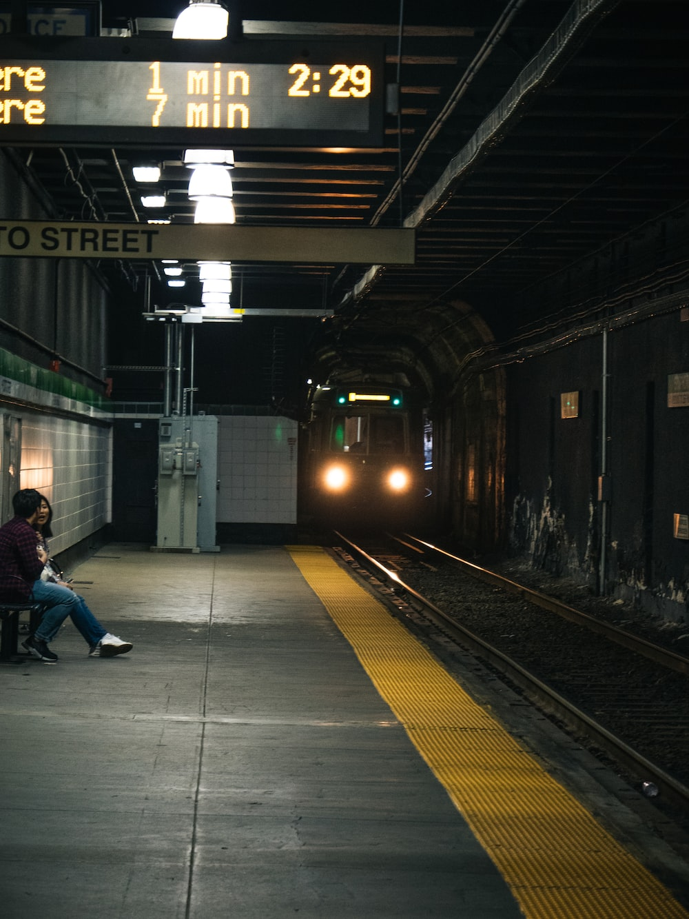 man and woman sits on bench near upcoming train