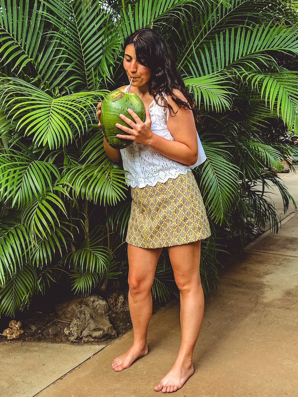 woman drinking coconut juice standing beside palm plant