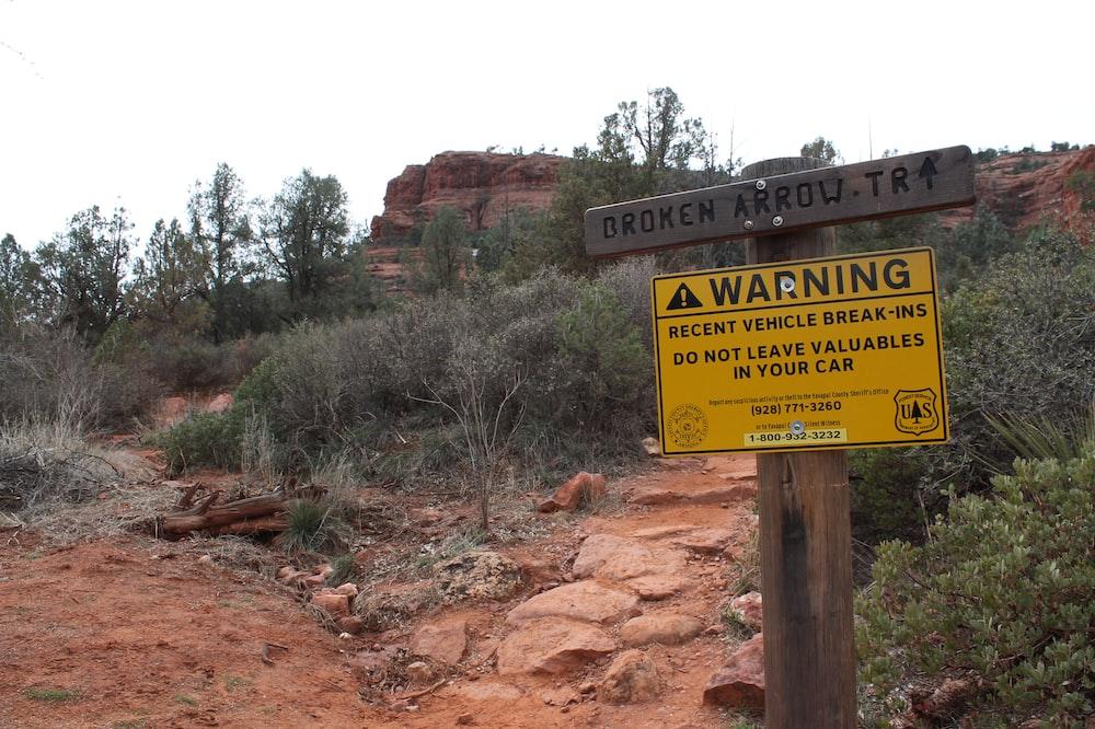 warning signage near trees during daytime