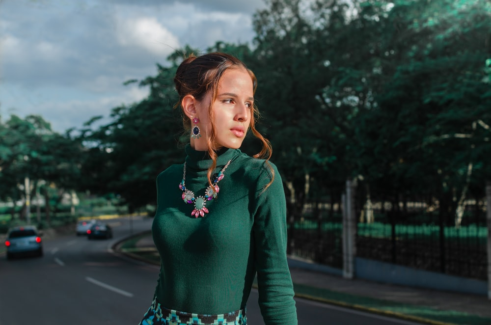 woman in green long-sleeved shirt posing near highway