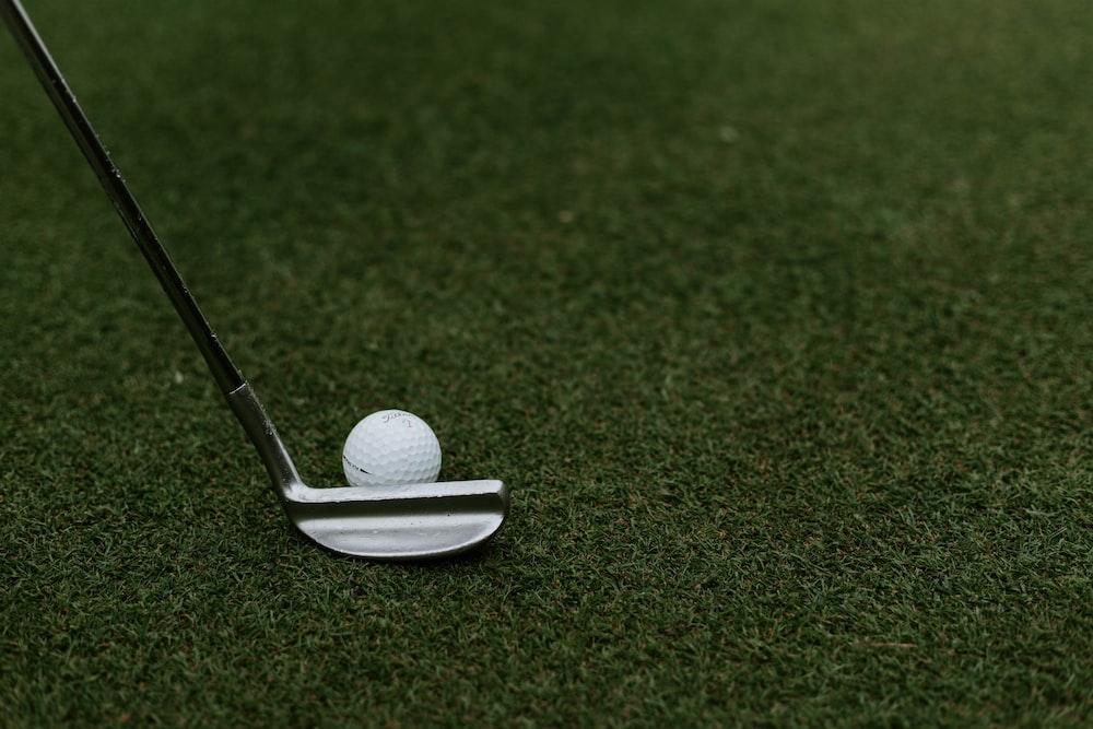 black and gray golf club beside golf ball on green grass field