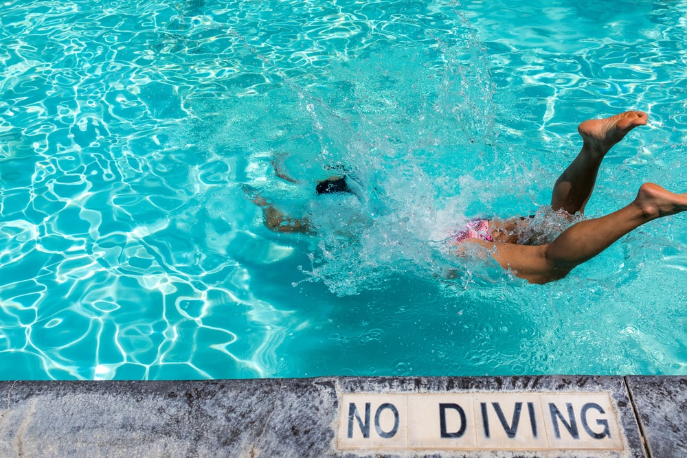 person diving on pool during daytime