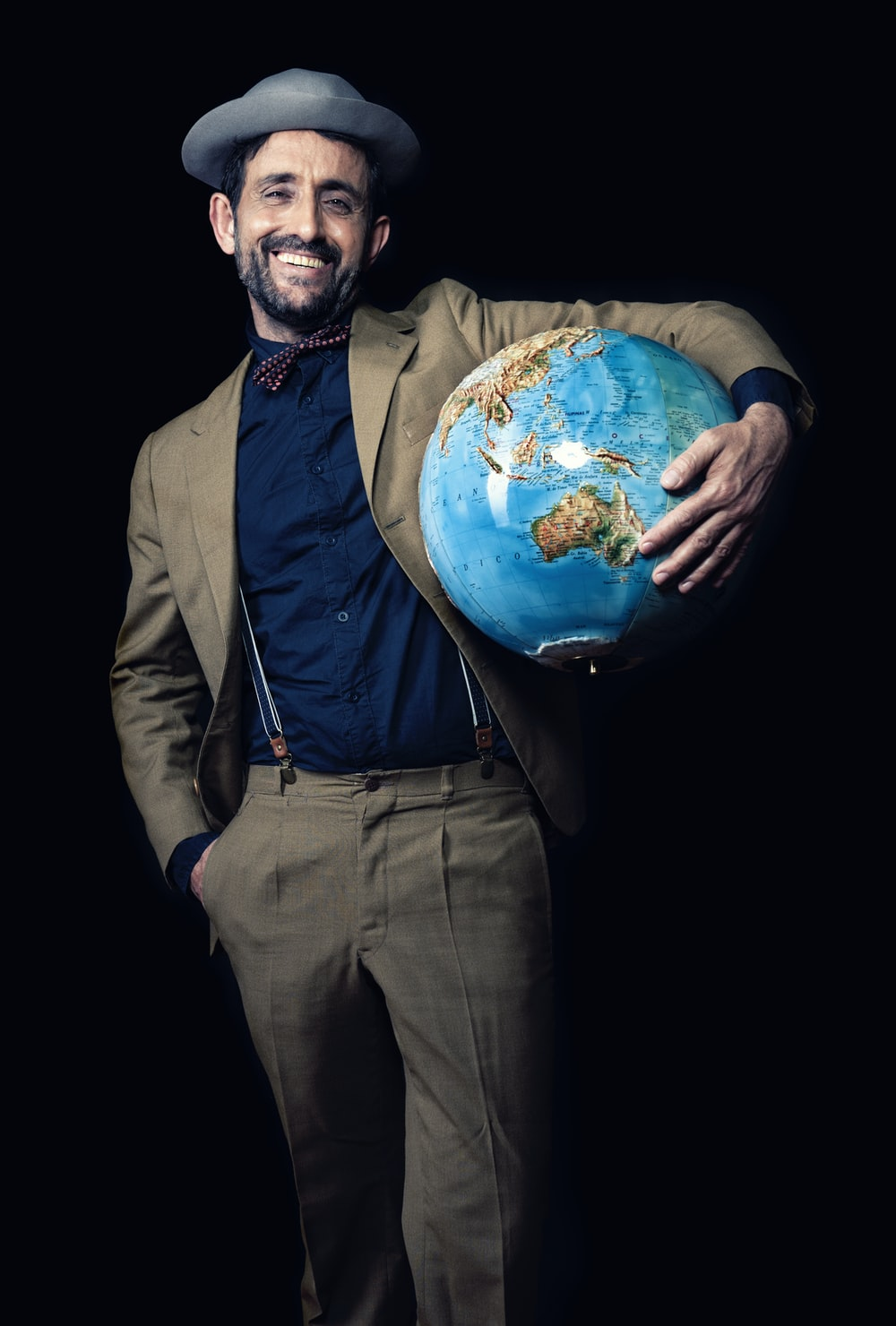 smiling man carrying blue globe