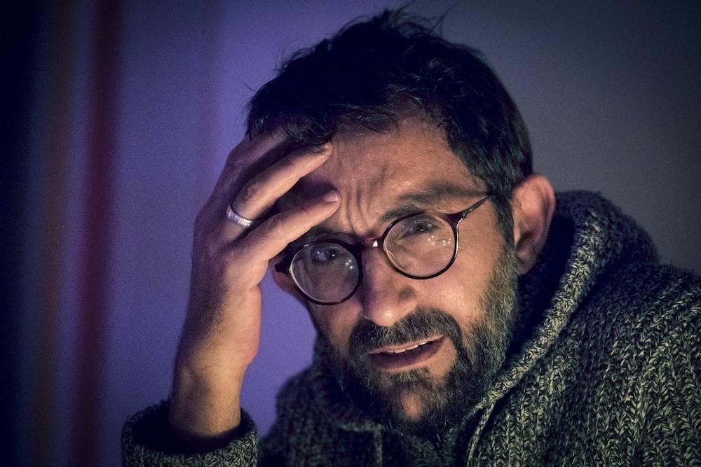 man in grey sweater and pair of black framed eyeglasses