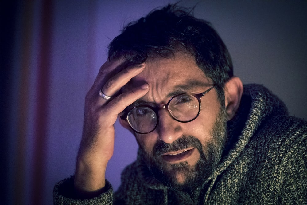 man in grey sweater and pair of black framed eyeglasses