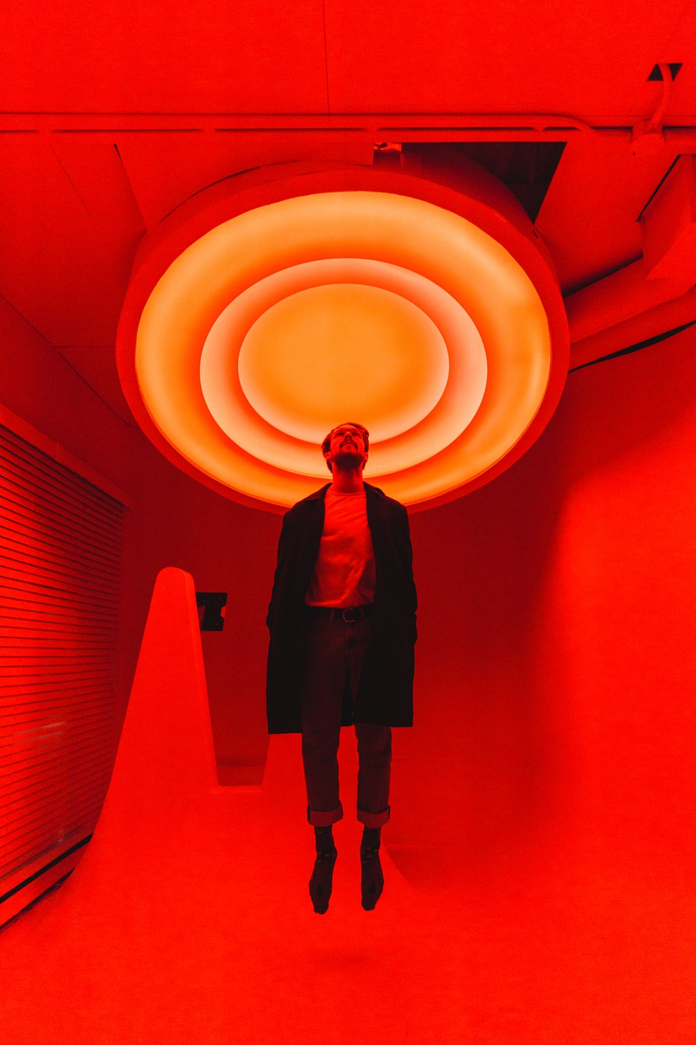man standing under large red light inside room