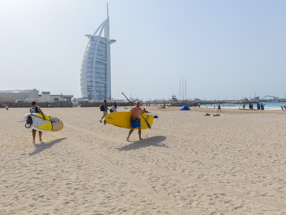 people walking and holding surfboards near Burj Al Arab building