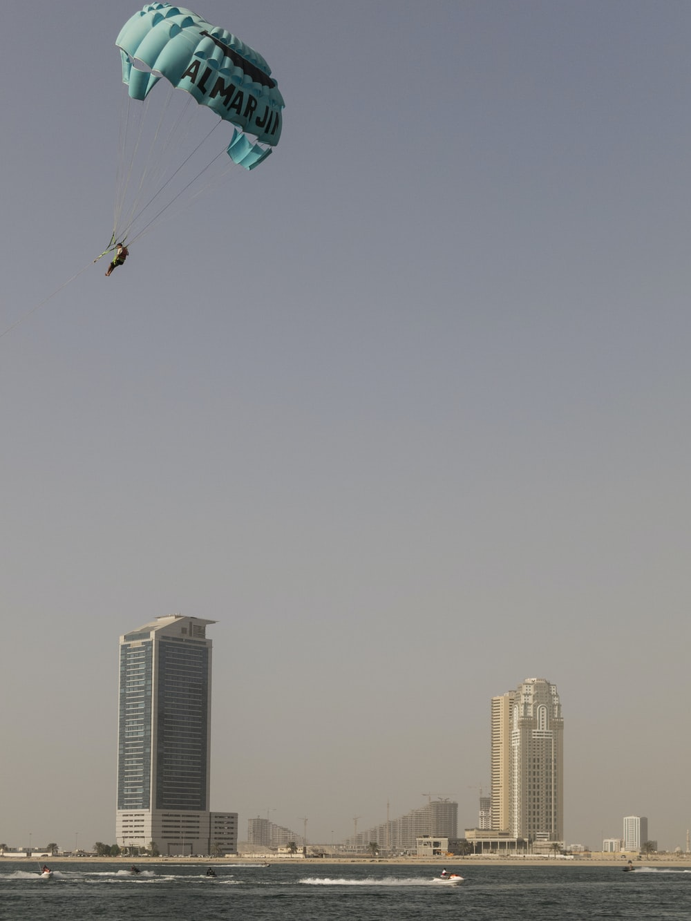 person in parachute above the water