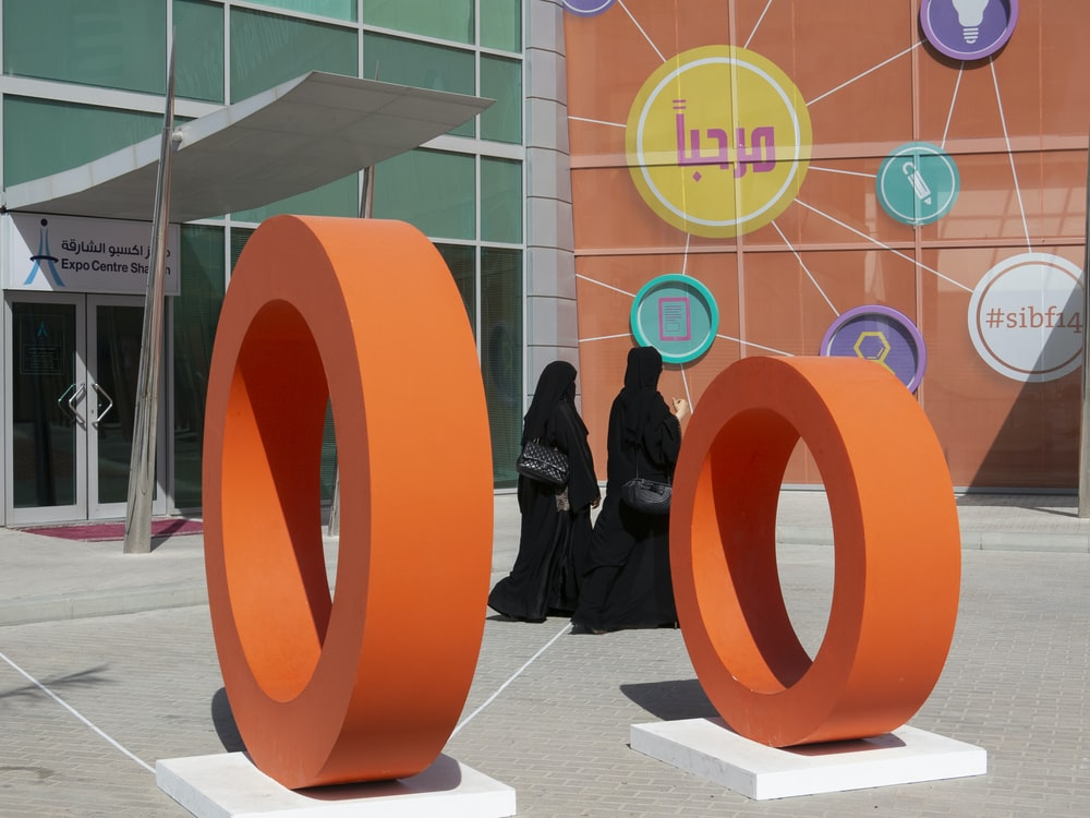 two orange rings statues outside the building