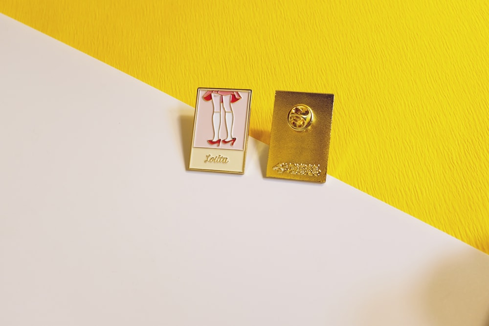 two gold and pink button pins on wall