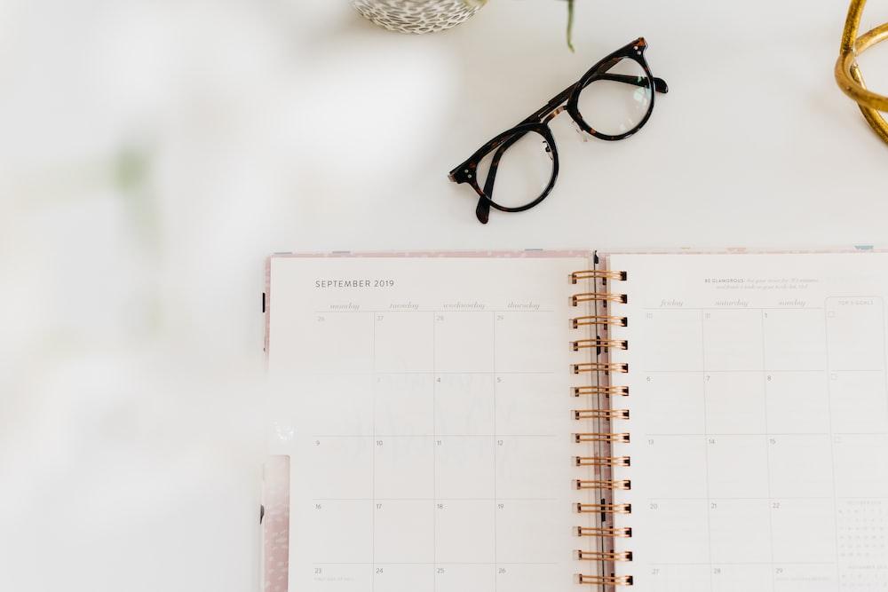 monthly planner book beside eyeglasses