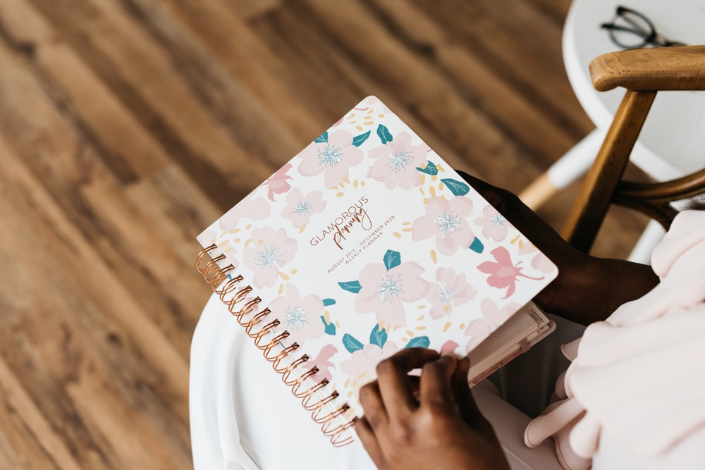 person in pink and green floral spiral notebook
