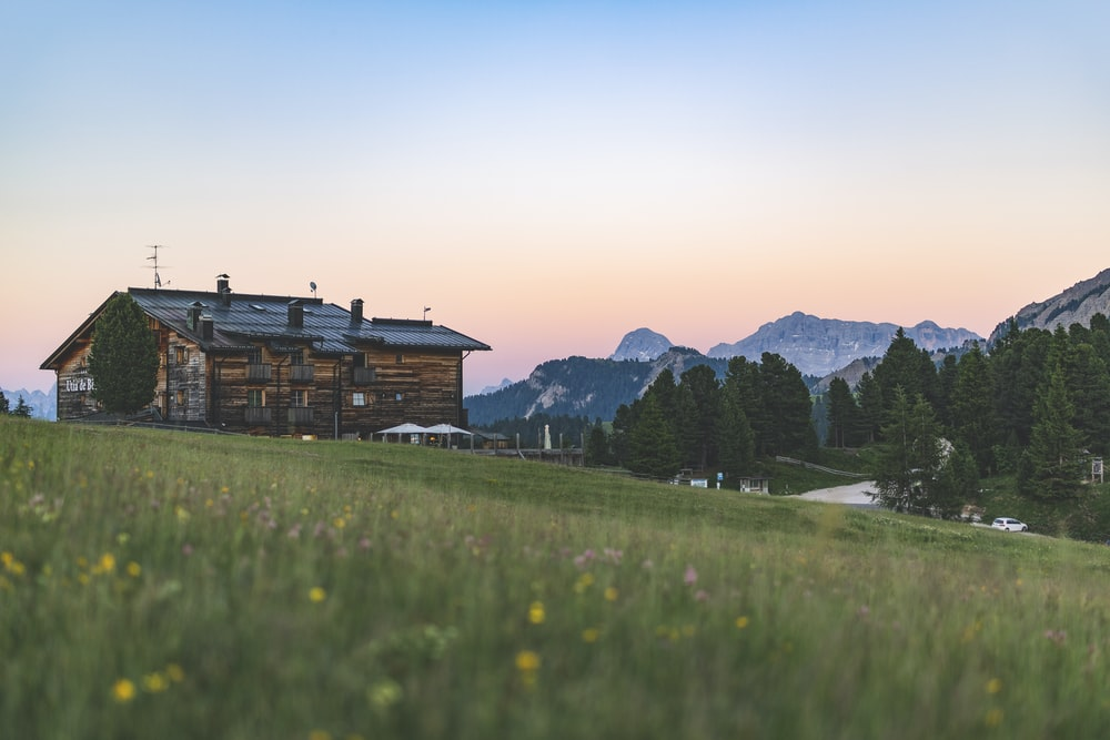 brown wooden house among grassy fields