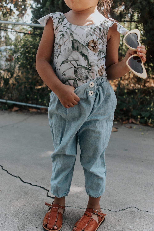 girl standing holding sunglasses