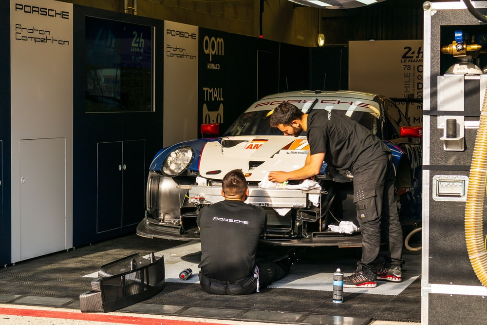 two men working on Porsche race car in pits