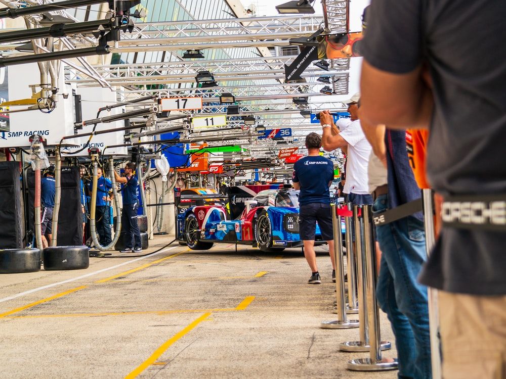 people standing near pit stop with red and blue car