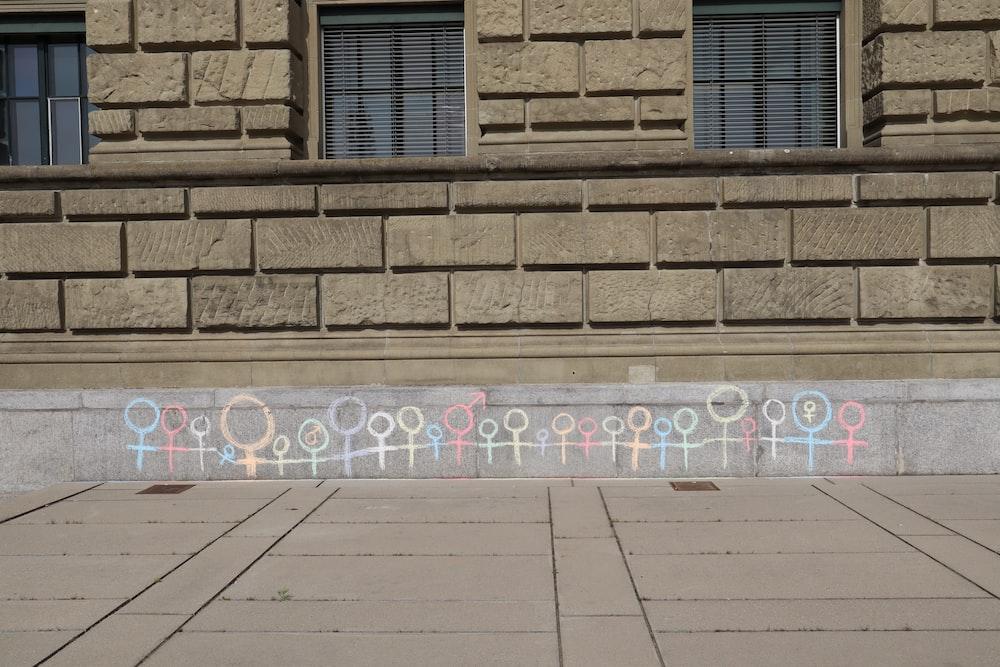 multicolored stick men painted concrete wall
