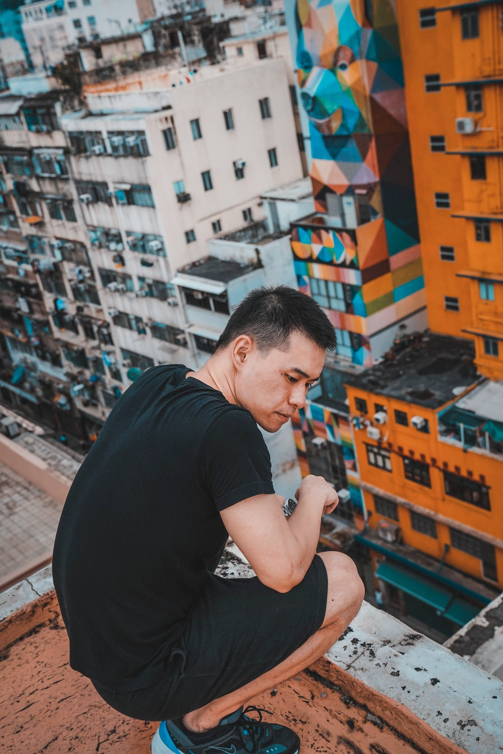 man squatting at the rooftop