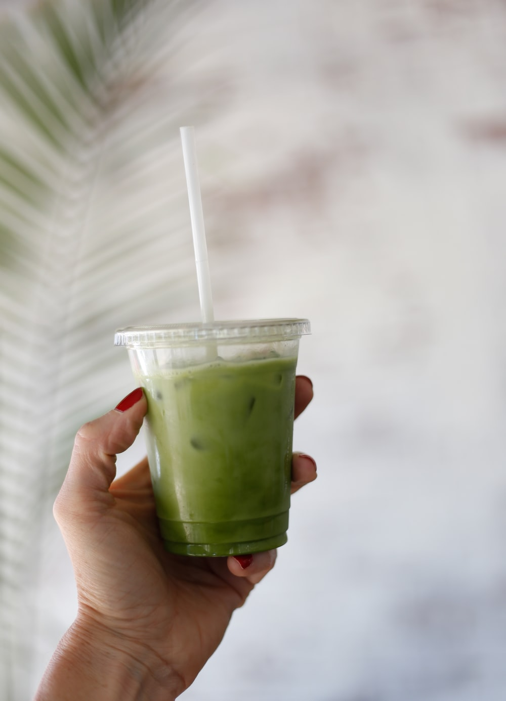green juice in clear disposable plastic cup