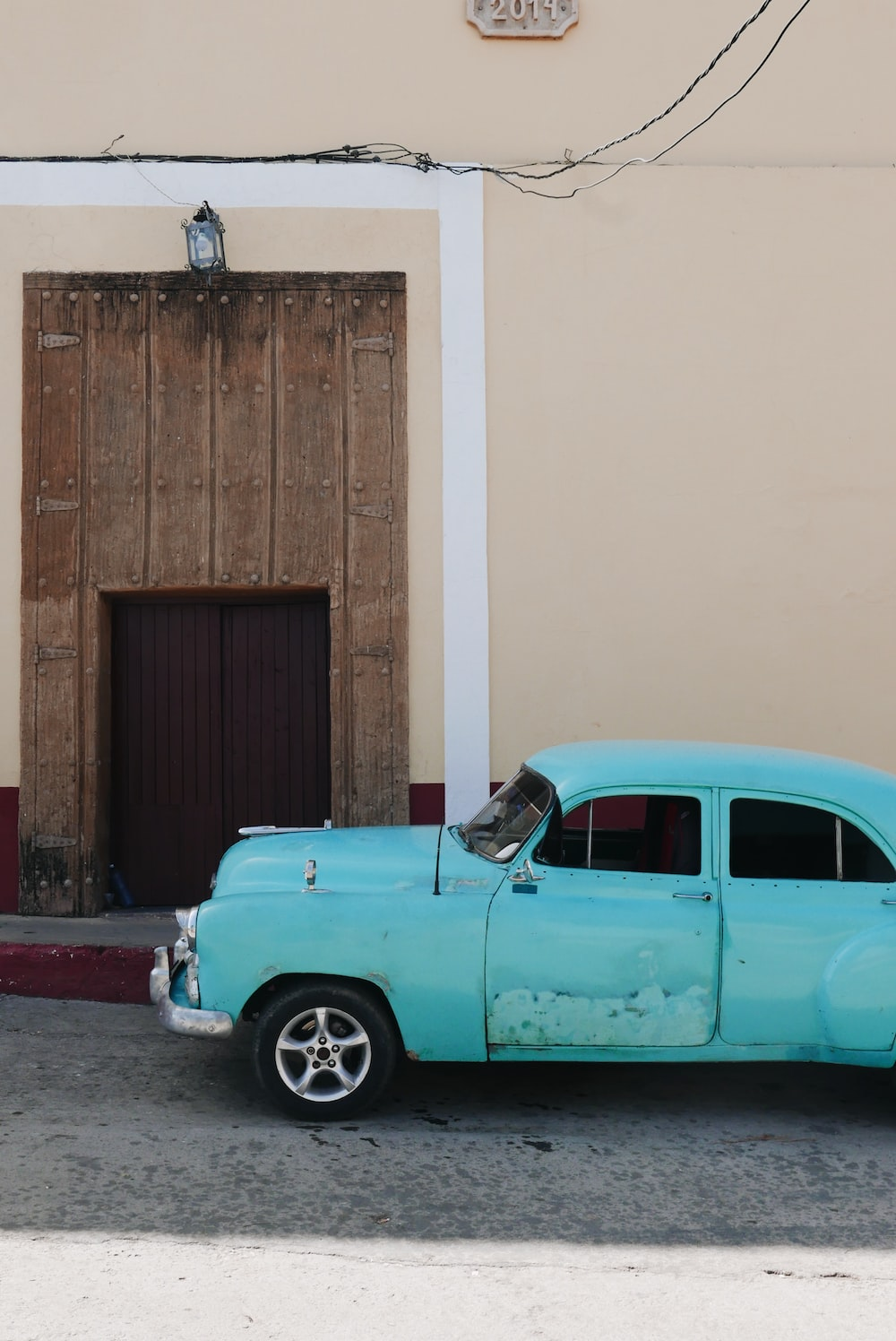 classic teal car parked beside the road near closed French doors