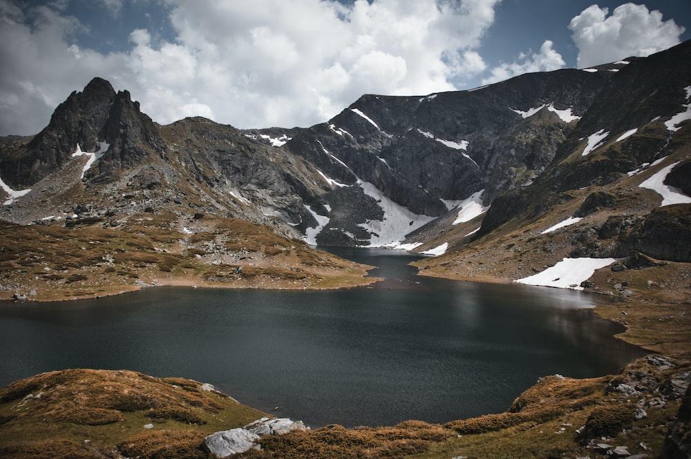 gray and brown mountains and lake