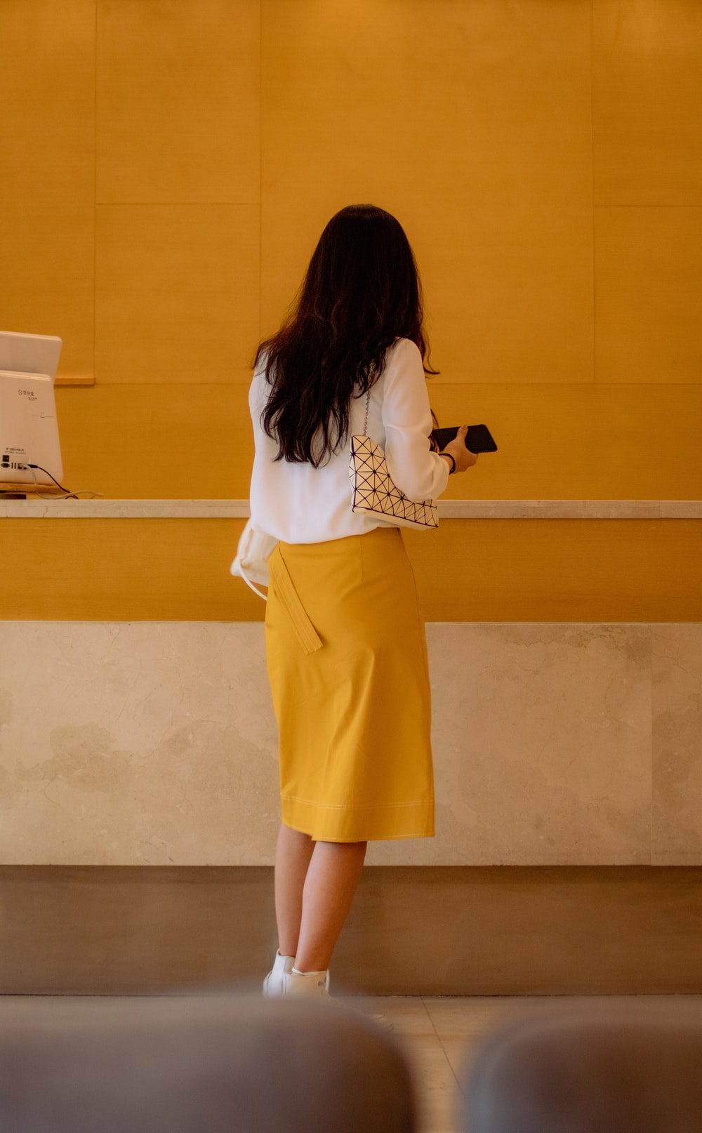 woman wearing white long-sleeved shirt and yellow skirt