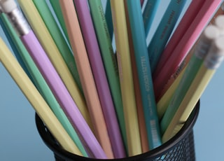 assorted-color wooden pencils on black mesh organizer