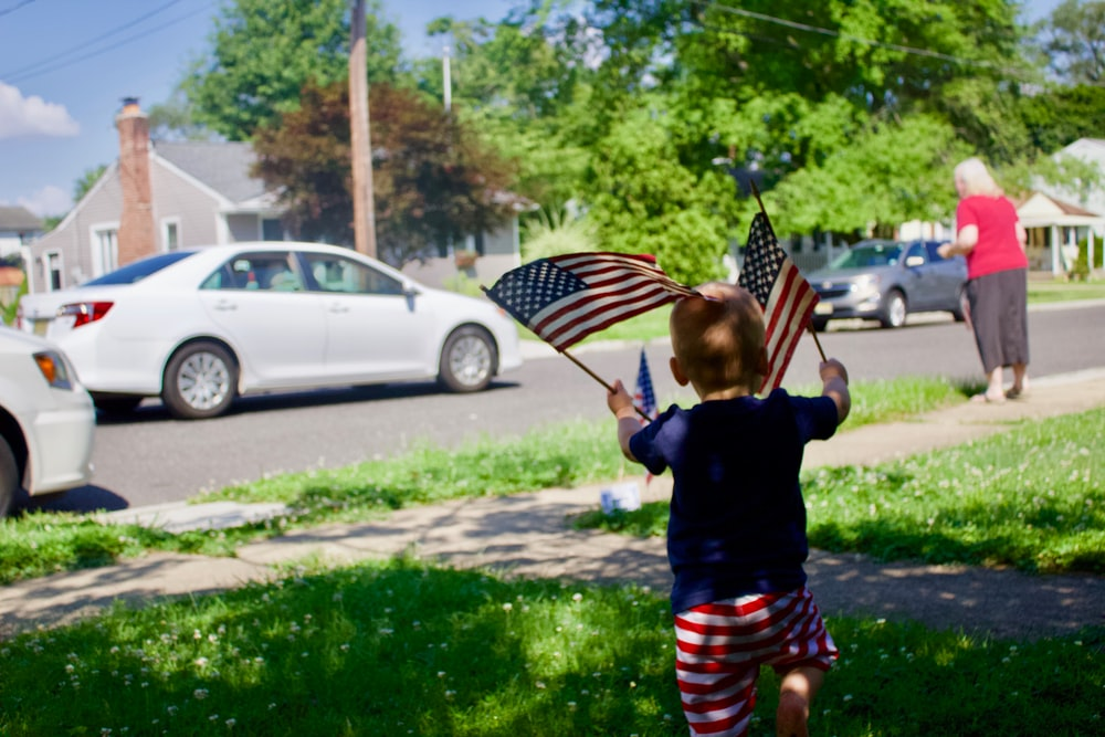 kid holding America flag during daytime