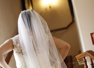 bride wearing gown and veil about to walk on staircase