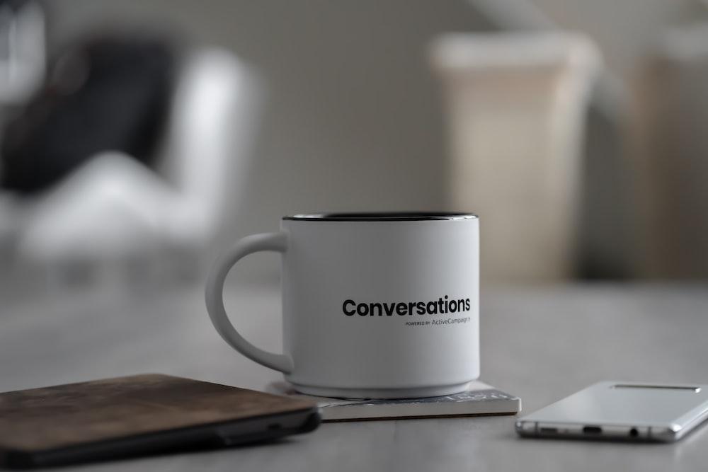 white conversations printed mug near smartphone