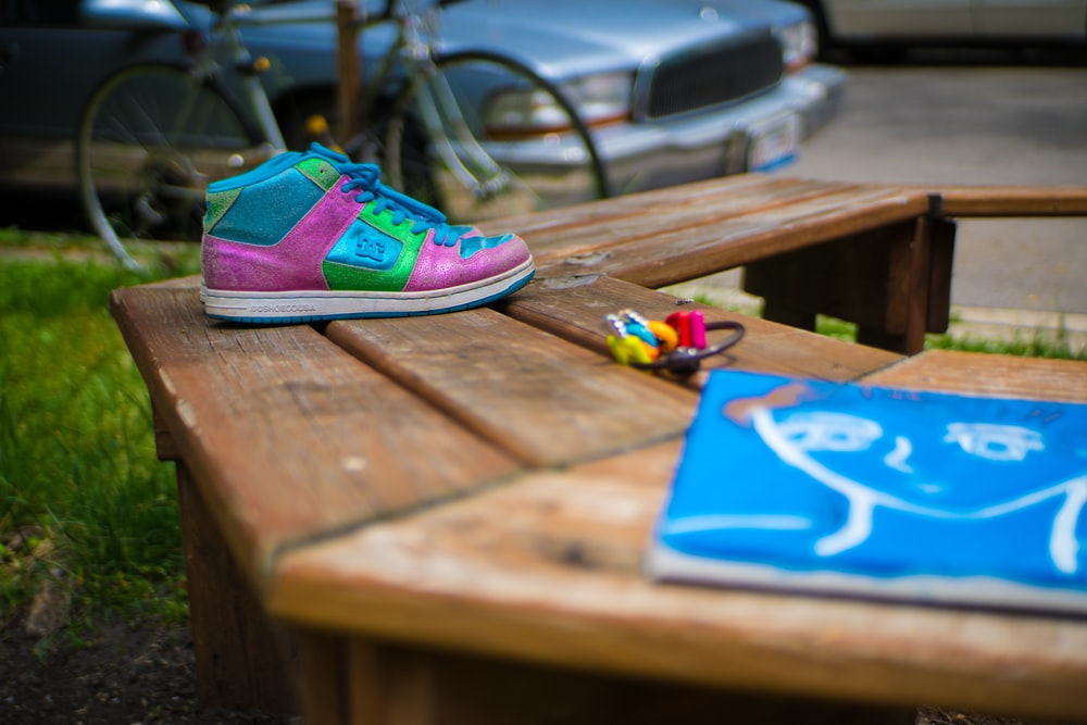 pink and teal high-top sneaker near blue softbound book