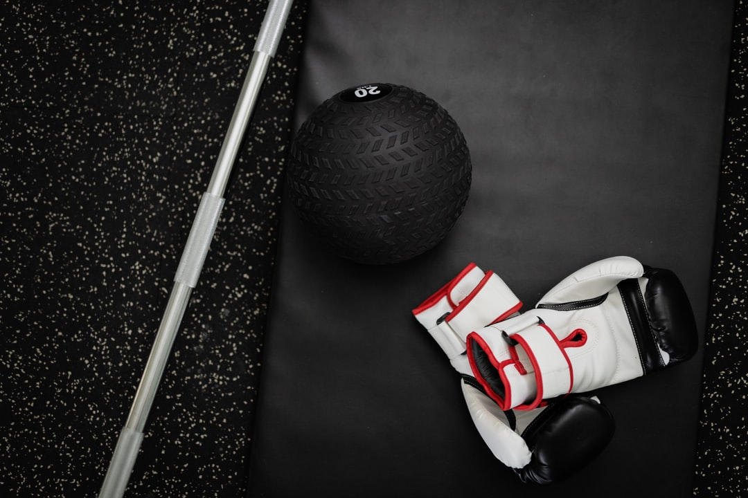 Workout gloves and weight ball sitting on a black mat in a gym