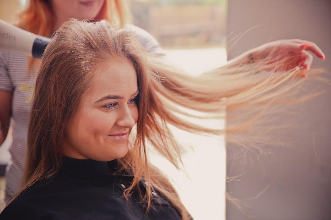Woman in salon having hair blown dry