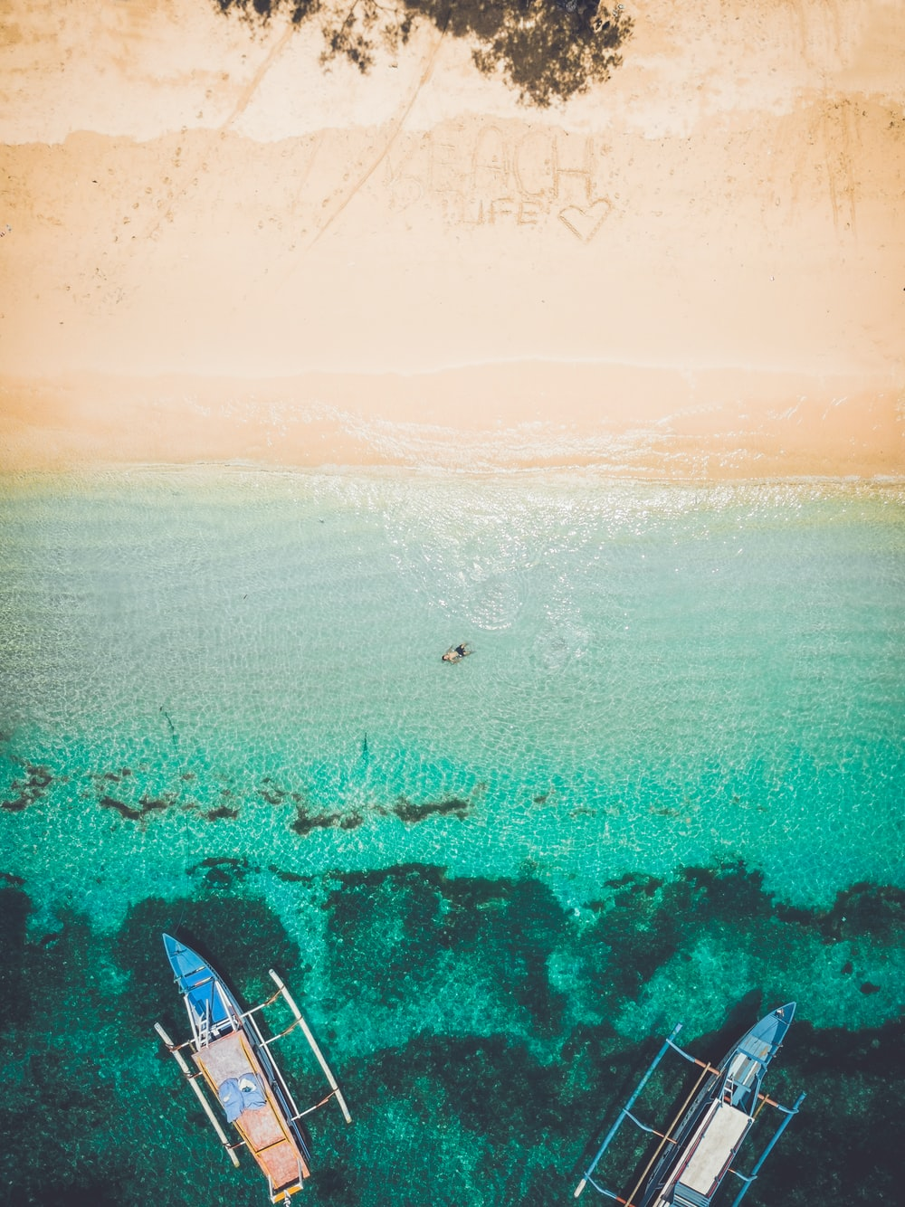aerial photography of seashore with two boatd