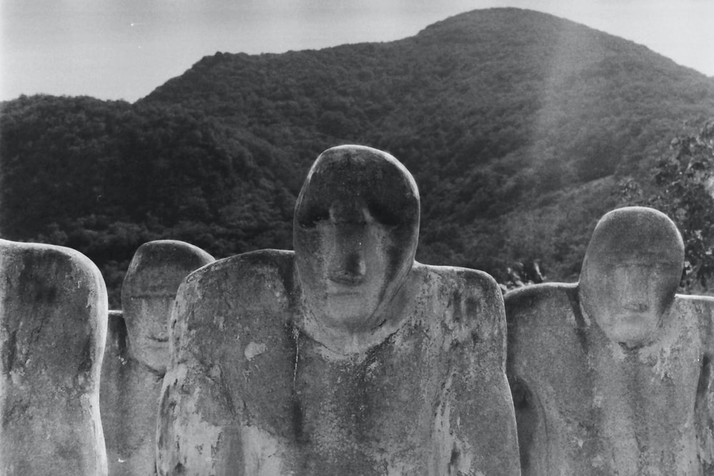 grayscale photography of statues near mountain