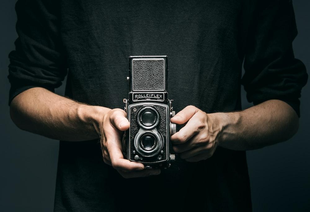 man holding vintage 2-lens camera