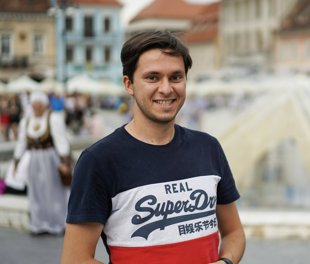 man wearing blue, white, and red crew-neck t-shirt
