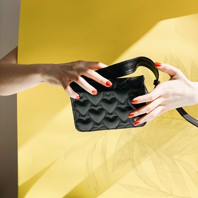 person's hand holding black leather bag