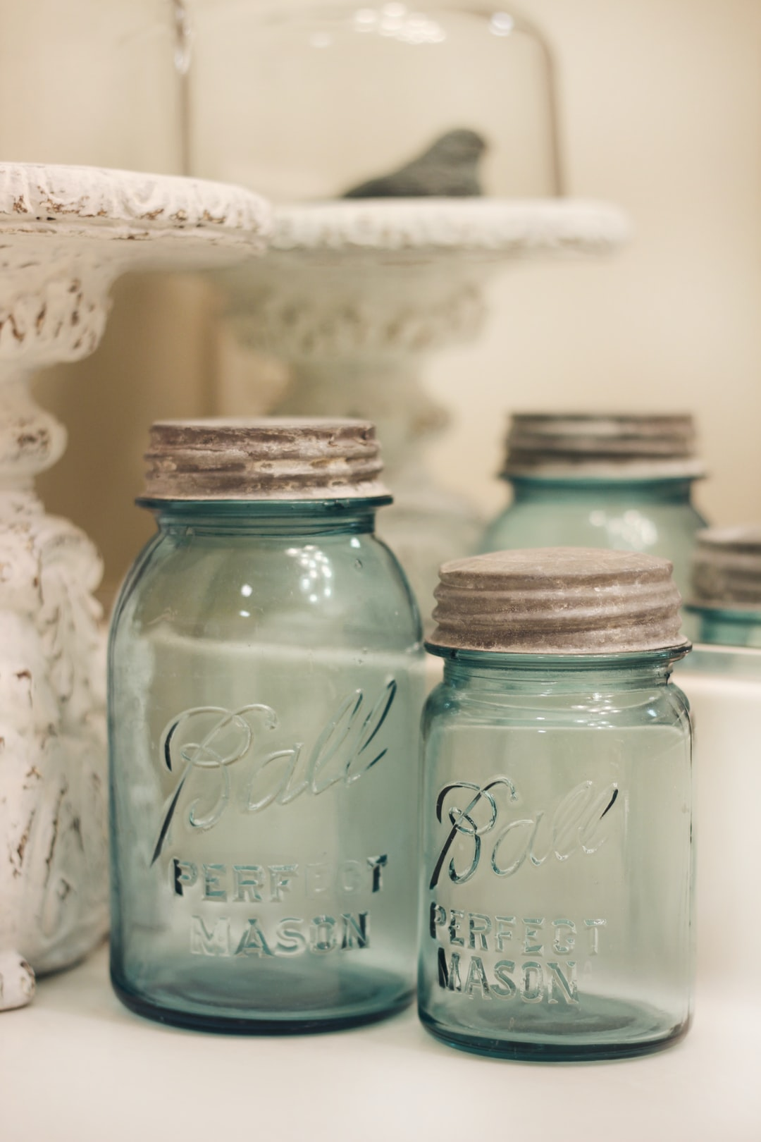 Vintage blue ball jars with zinc lids are displayed on a bathroom countertop as part of farmhouse style decor. Clean white bathroom with vintage objects for decor make this an appealing design choice.