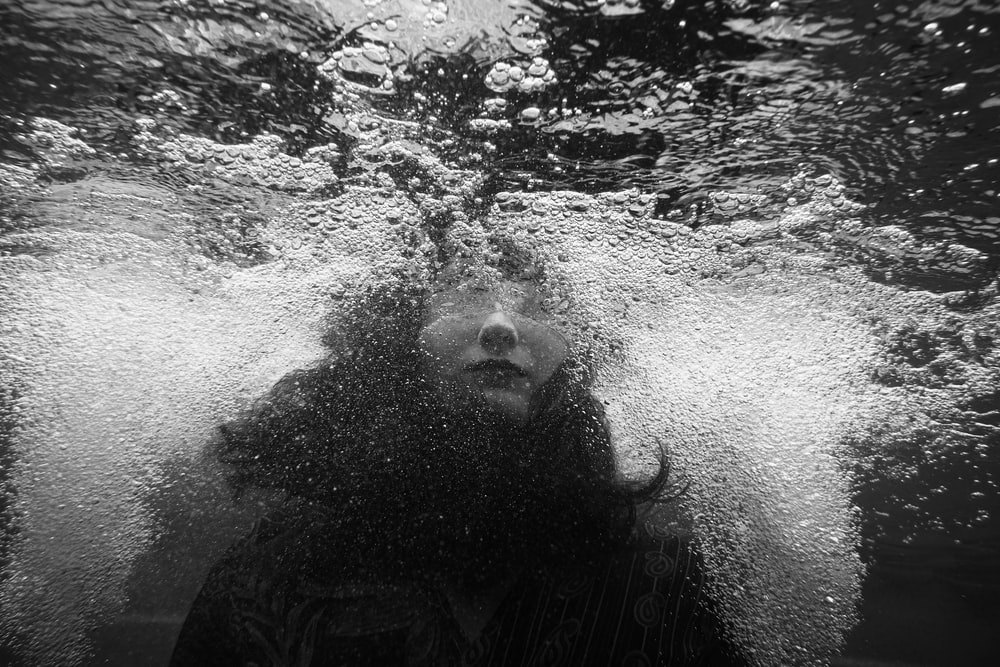 grayscale photo of person underwater