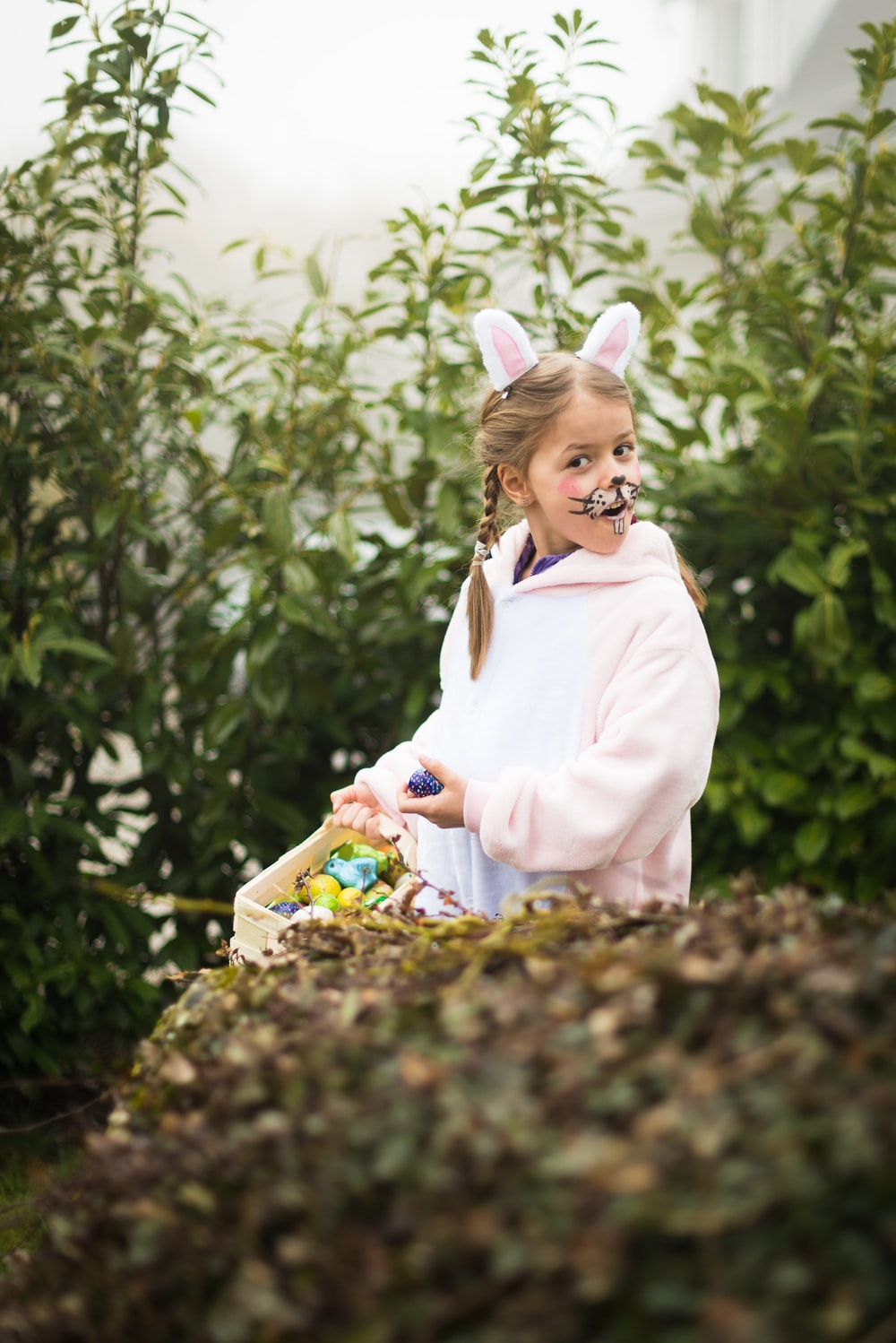 girl in pink hoodie with bunny costumes near green plants